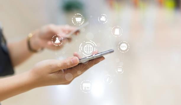 スマートフォンを使用して若い若い女性をクローズアップし、オンラインショッピングのための市場のウェブサイト上の項目を選択します。アイコン仮想インターフェイス技術コンセプト - アイコン プレゼント ストックフォトと画像