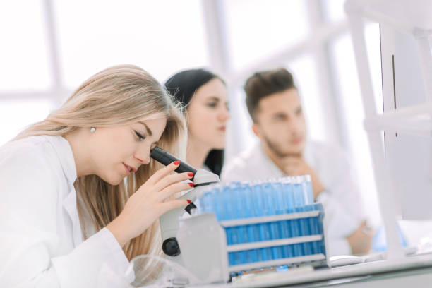 close up.a modern female scientist looks into a microscope in a laboratory - medical technology стоковые фото и изображения