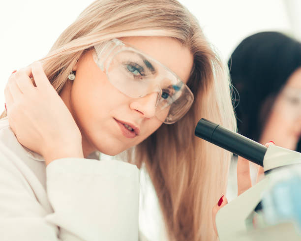 close up.a modern female scientist looks into a microscope in a - medical technology стоковые фото и изображения