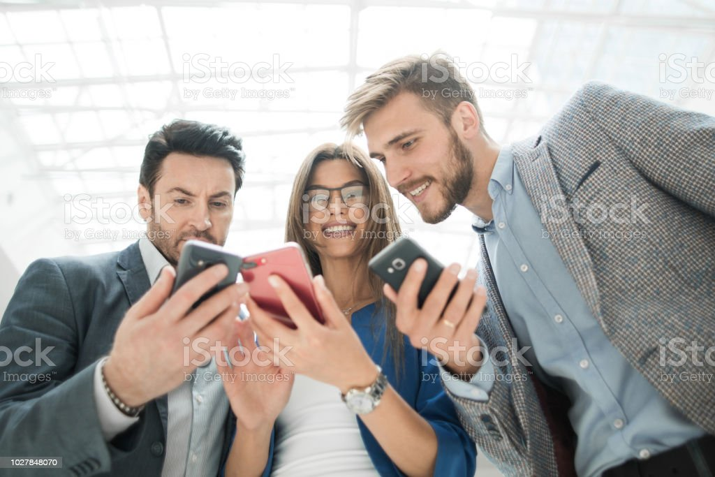 close up.business colleagues reading SMS on their smartphones stock photo