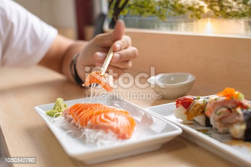 Close up,Hand holding salmon sashimi using chopsticks - Raw fresh salmon sliced served on white dish with wasabi, Japanese food style.