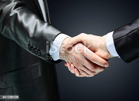 istock close up.handshake of business partners on dark background 941268208