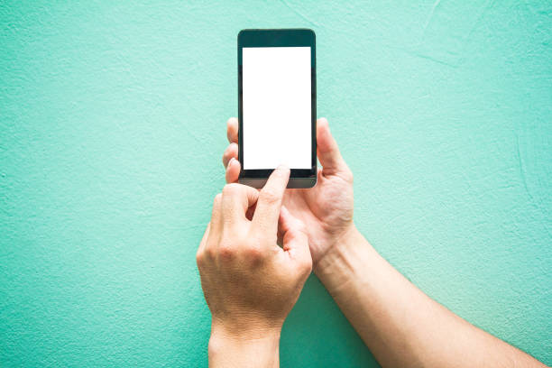 Close up.Man holding Touching mobile phone Space left on wall  pastel color stock photo