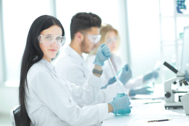 close up.modern woman sitting with colleagues at the laboratory table. - medical technology стоковые фото и изображения