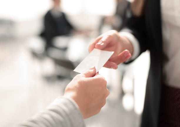 close up.two business woman exchanging business card - business card stock photos and pictures