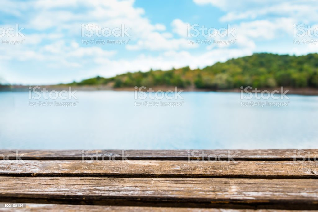 Close view of an old wooden table. Blue lake and sky in the background. royalty-free stock photo