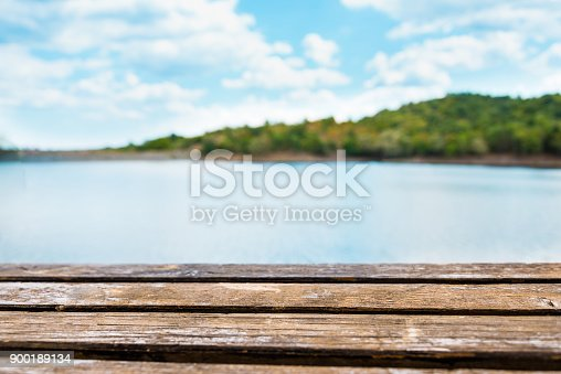 Close view of an old wooden table. Blue lake and sky in the background.