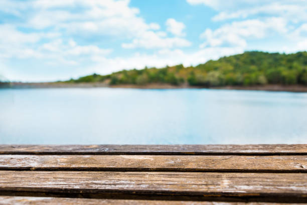 Close view of an old wooden table. Blue lake and sky in the background. stock photo