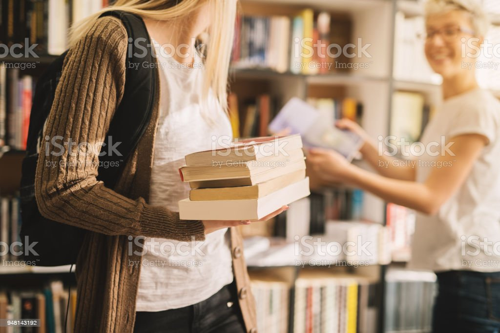 Close view of book stack held by a young high school student girl in the library. stock photo