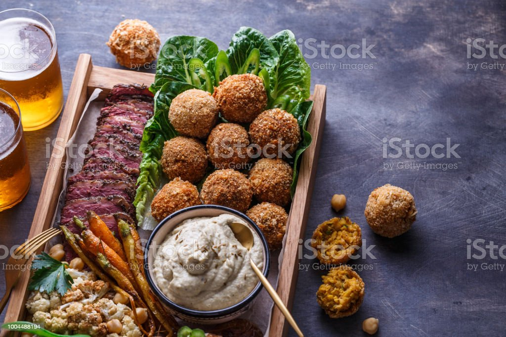Close view of falafel, babaghanoush and pastrami in the wooden box, copyspace. stock photo