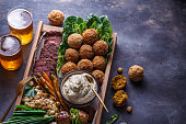 istock Close view of falafel, babaghanoush and pastrami in the wooden box, copyspace. 1179124880