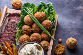istock Close view of falafel, babaghanoush and pastrami in the wooden box, copyspace. 1179124884