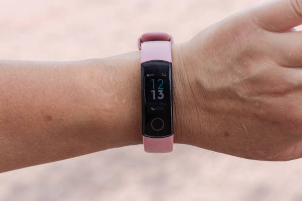 Close view of fitness tracker on wrist of female. Active living concept. Close view of fitness tracker on wrist of female. Active living concept. fitness tracker stock pictures, royalty-free photos & images