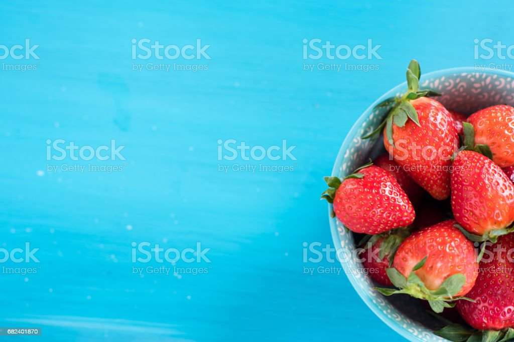 close view of somefresh strawberries in a bowl isolated on a blue background royalty-free stock photo