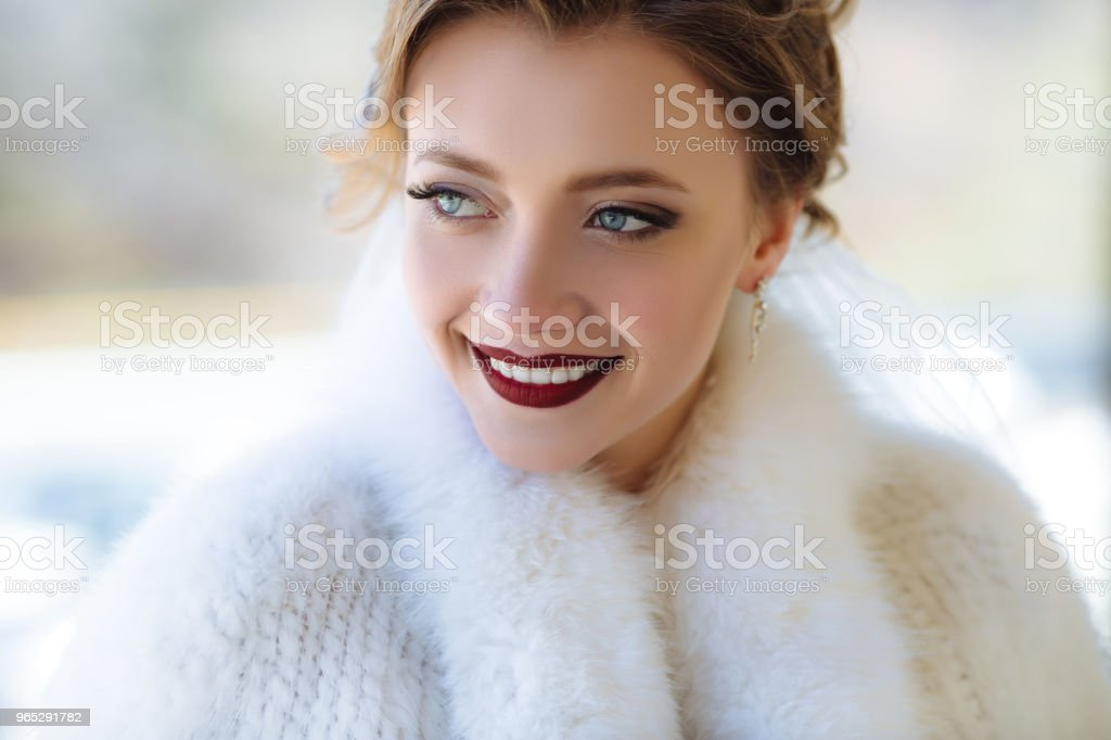 A close view of the face of a young girl with a scarlet lip color. The model is smiling broadly and showing white teeth, staring into the distance with blue eyes. Close-up portrait - Zbiór zdjęć royalty-free (Biały)