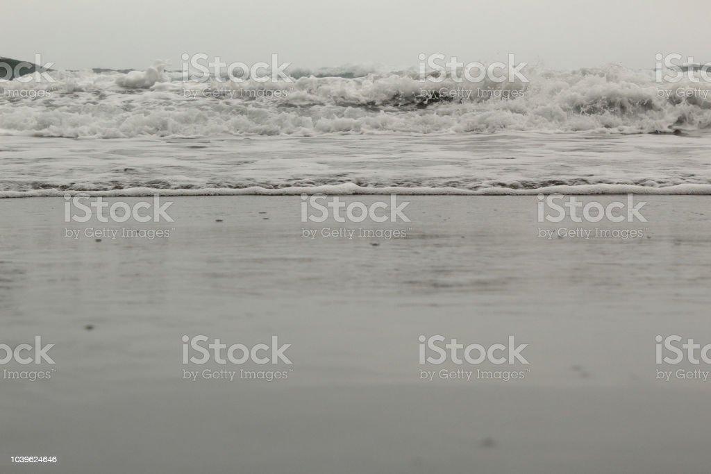 A Close View Of The Sea Undertow In The Almaciga Black Sand Beach In