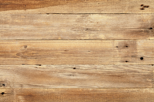 A close-up view of the texture of a wooden table.  The table is made from light-colored wood and has some dark spots on the left and right sides.  There is also a dark spot in the middle of the table toward the bottom.  The wood at the top and bottom of the table is darker than the wood in the center of the table.  The piece of wood at the top of the table also appears to have a dark stain on it.  The close-up gives a direct view from above the table, revealing cracks and knotholes in the wood.