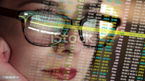 Stock photo of a beautiful young woman's face very close up. She's looking at a complicated set of holographic, see-thru numbers. The numbers are also reflected in her spectacles.