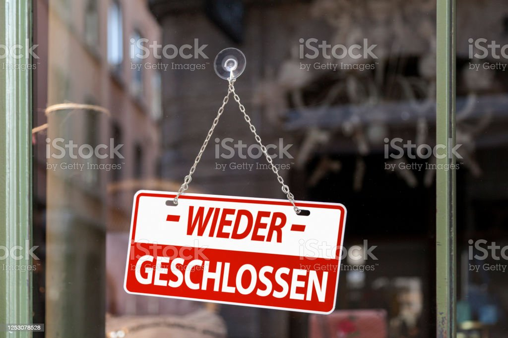 """Closed again - Closed sign Close-up on a red sign in a window written inside in German """"Wieder geschlossen"""" meaning in English """"Closed again"""". Bar - Drink Establishment Stock Photo"""