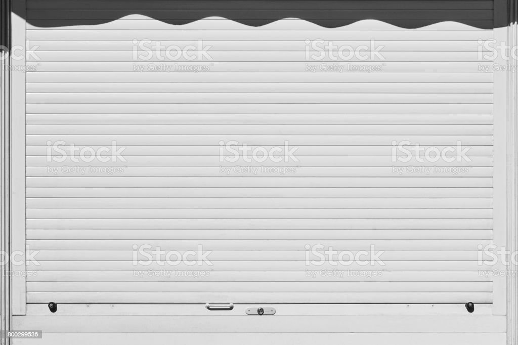 Closed and locked white rolling shutter. Security background. stock photo