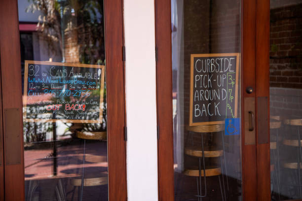 Closed bar during Covid-19 pandemic A  sign in a bar, closed due to the Covid-19 pandemic, announces curbside pickup in Santa Barbara, CA curbsidepickup stock pictures, royalty-free photos & images