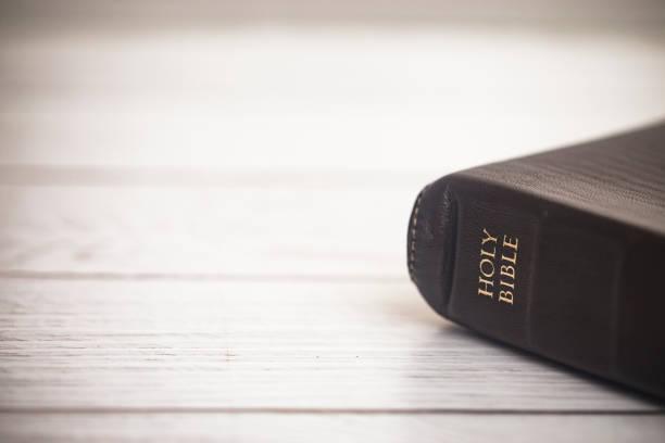 geschlossene bibel auf einem holztisch - bible stock-fotos und bilder