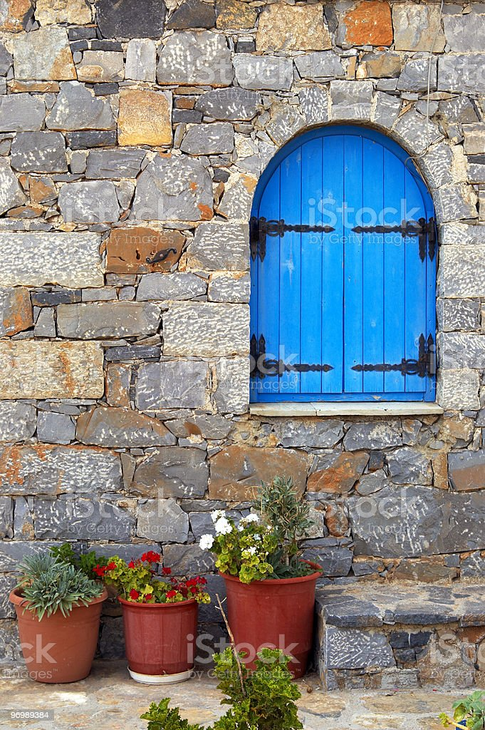 Closed blue window and geraniums royalty-free stock photo