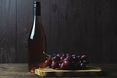 A closed bottle of rose wine and a bunch of red seedless grapes near on a wooden background. Place for text.