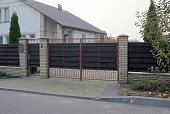istock closed brown gate and part of the fence made of wooden boards and bricks 1196271846