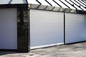 closed business shop or store front with roller shutters - economy crisis and recession concept