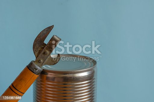 Closed can and can opener. Canned food and a special knife. Long-term storage products. Close-up. Copy space.