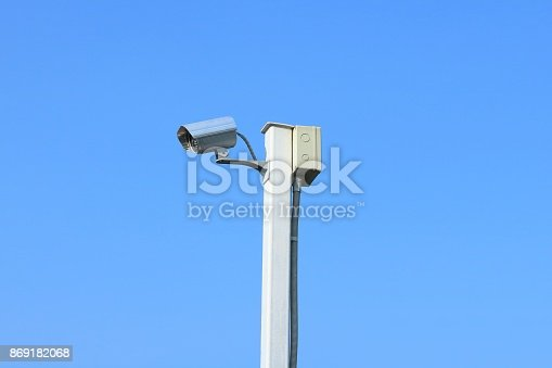 istock Closed circuit television camera on white steel pole with the background of blue sky. 869182068