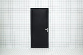 istock Closed dark, black door in the middle. White, ceramic tiles wall and floor. Empty place for text or objects. Front view. 1045860302