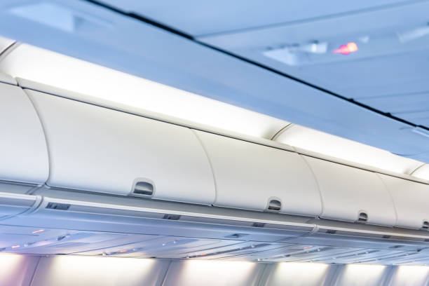 Closed doors luggage shelves in economy class passenger aircraft. Closed doors luggage shelves in economy class passenger aircraft overhead projector stock pictures, royalty-free photos & images
