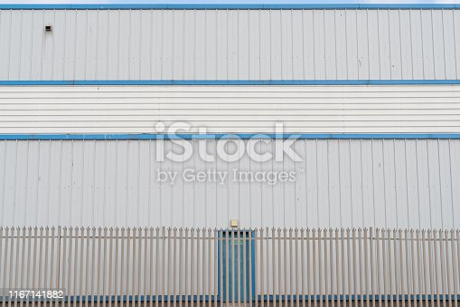 Closed doorway on the exterior of a large industrial building constructed of prefabricated steel panels.  Belfast, Northern Ireland.