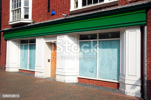 Bankrupt closed down retail shop, with whitewashed windows, at a pedestrian shopping centre