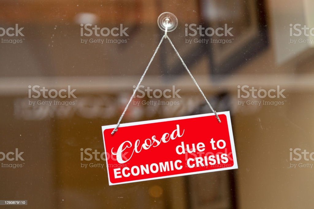 """Closed due to economic crisis - Closed sign Red sign hanging at the glass door of a shop with written in it """"Closed due to economic crisis"""". Business Stock Photo"""