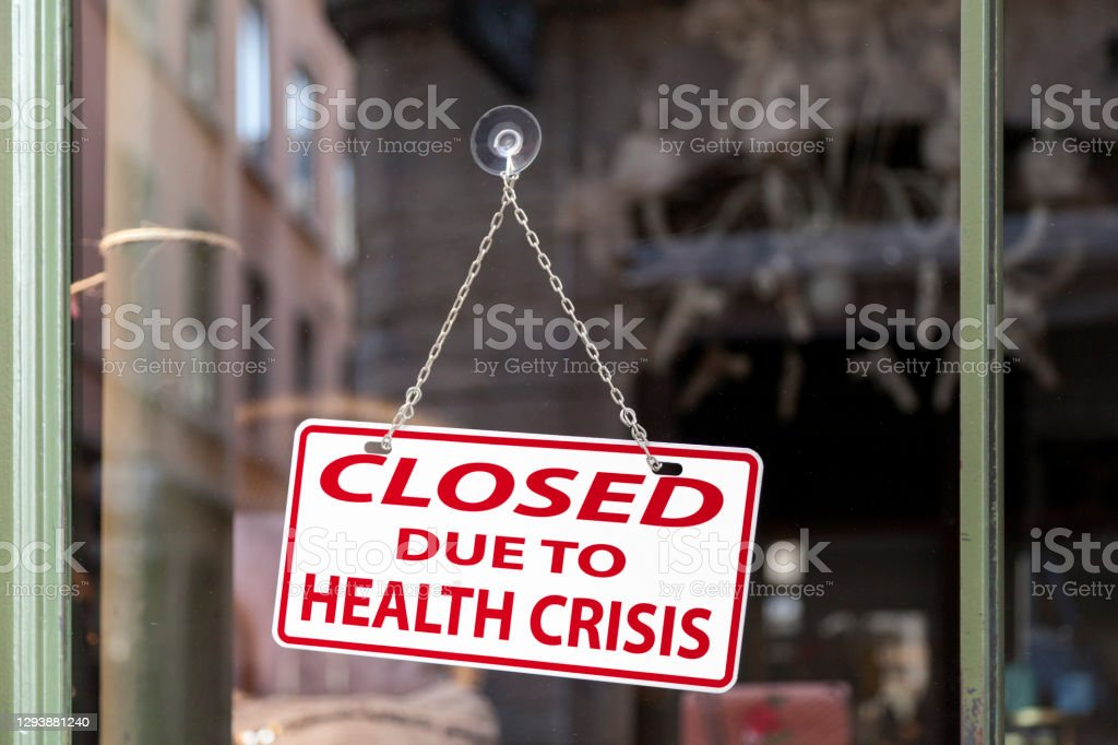 """Closed due to health crisis - Closed sign Close-up on a red and white sign in a window with written in it """"Closed due to health crisis"""". Bankruptcy Stock Photo"""