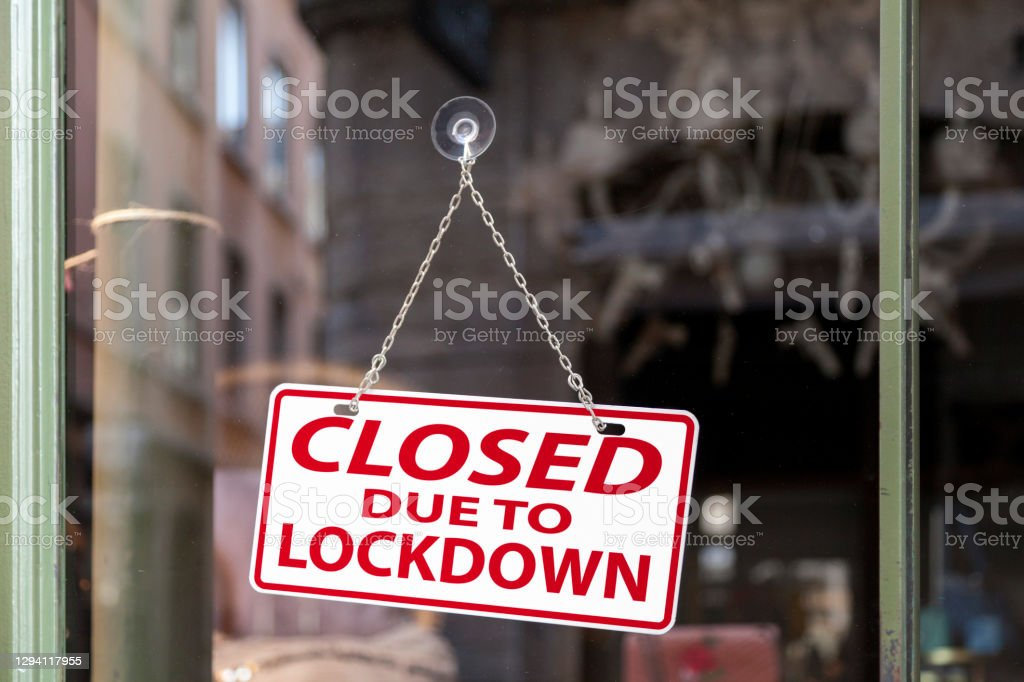 """Closed due to lockdown - Closed sign Close-up on a red and white sign in a window with written in it """"Closed due to lockdown"""". Bankruptcy Stock Photo"""