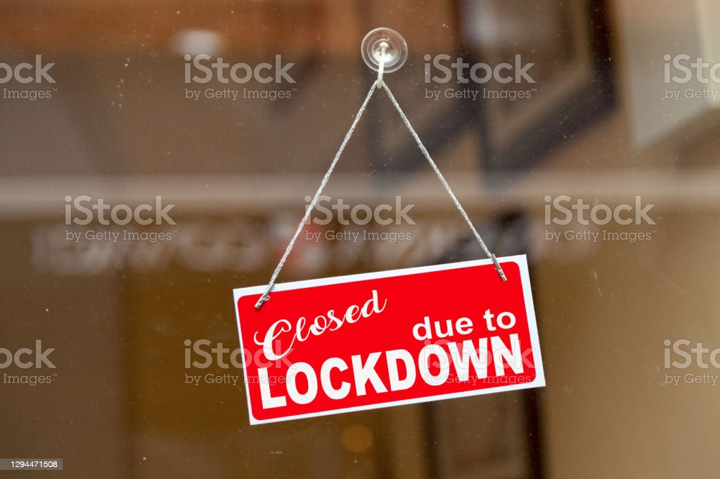 "Closed due to lockdown - Closed sign Red sign hanging at the glass door of a shop with written in it ""Closed due to lockdown"". Business Stock Photo"