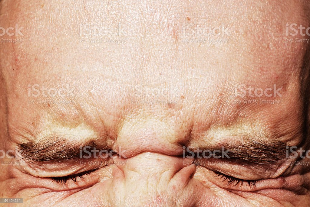 closed eyes squinting and forehead stock photo