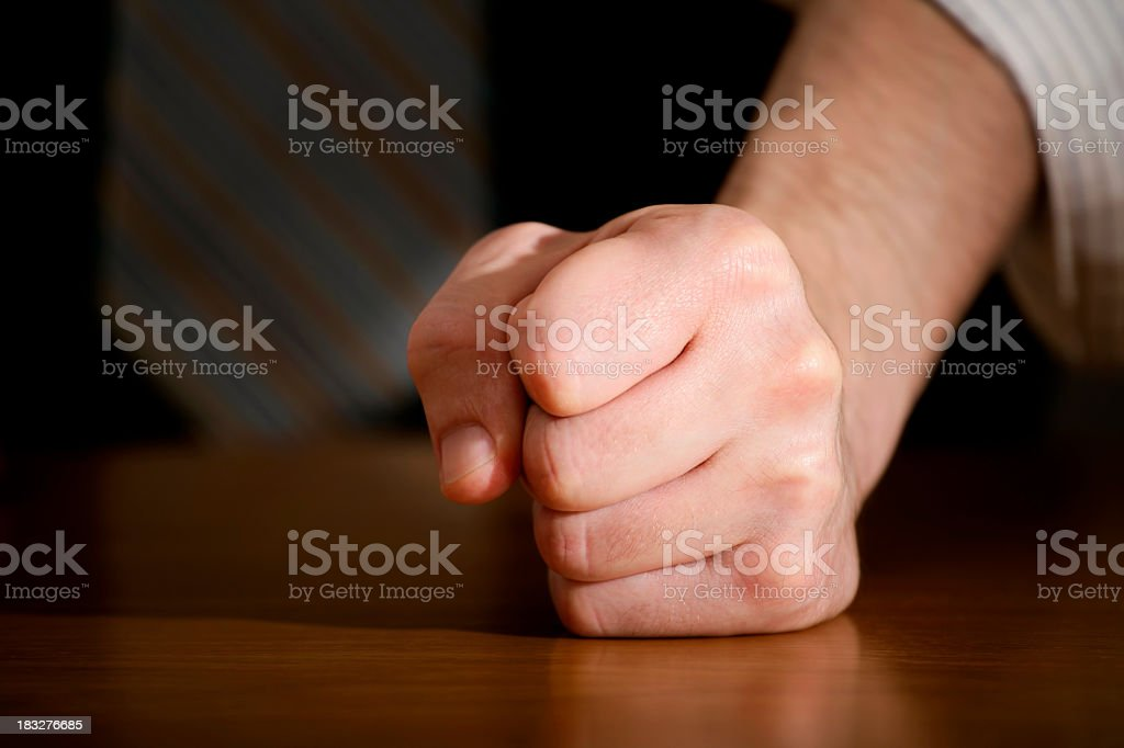 A closed fist on a shiny wooden table stock photo