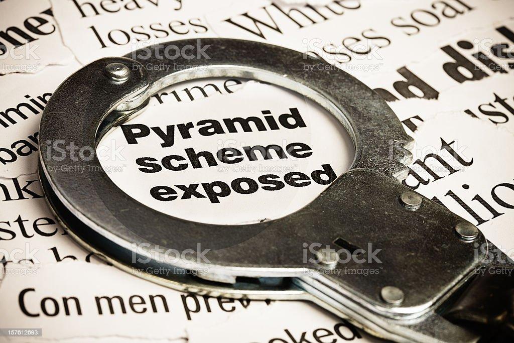 Closed handcuff on headline: pyramid scheme exposed stock photo