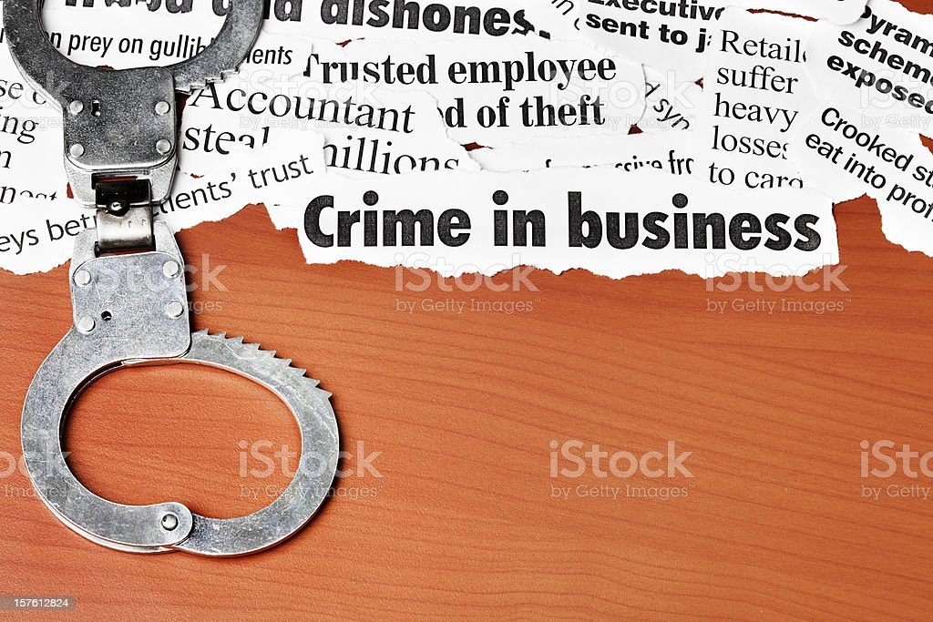 Closed handcuffs rest on white collar crime headlines stock photo