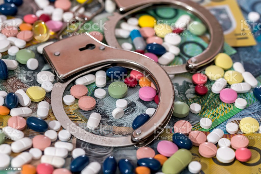 Closed handcuffs with colourful pills on australian dollar background stock photo