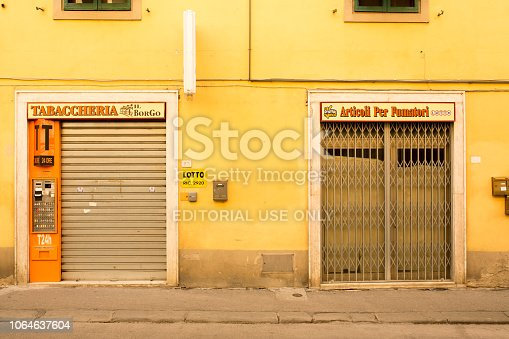 CERTALDO, ITALY - SEPTEMBER 2016. Yellow facade and a closed tobacco store in the old city of Certaldo.