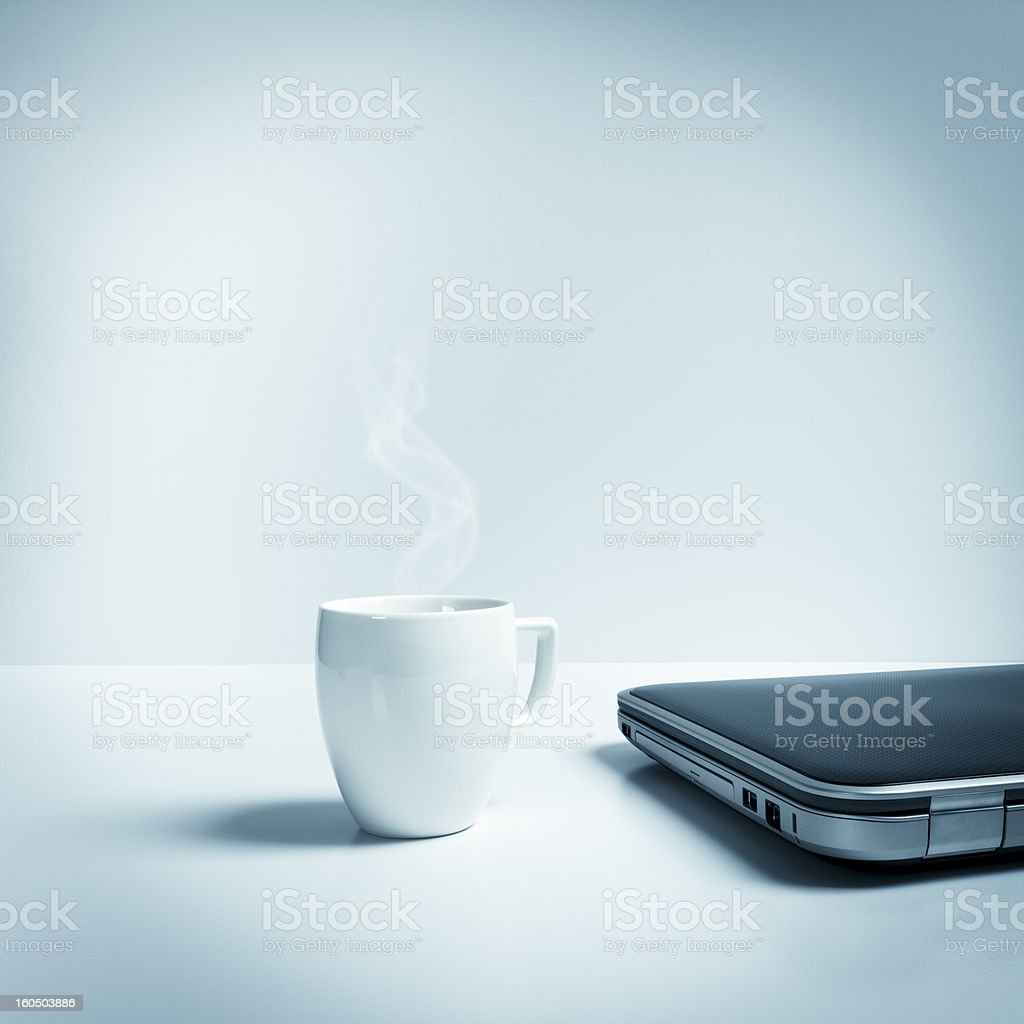 Closed laptop with mug of hot tea, coffee, blue toned stock photo