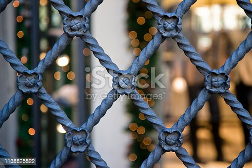 Closed metal grate with ornate elements.