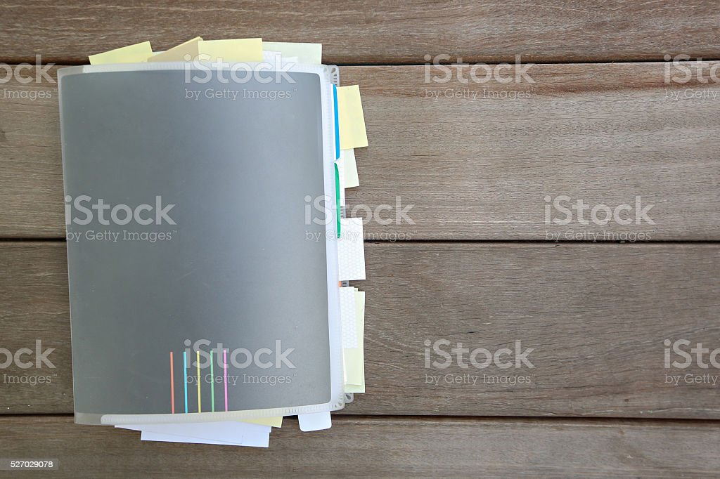 Closed notebook with many sticky notes inside stock photo