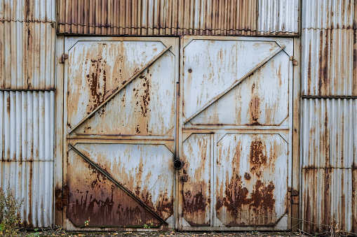 Closed old rusty iron gate sash in a corrugated iron wall. Abandoned industrial building. Grunge